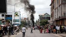 People look on as protesters burn tyres during a demonstration calling for the President of the Demo