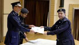 Assistant Director of the Police Training Institute, Major Ali Saud al-Hanzab, gives away the certif