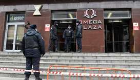 Russian police officers gather at the entrance to a business centre, which houses the office of oppo