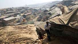 Rohingya refugees walk along the Kutupalong refugee camp in Cox's Bazar, Bangladesh