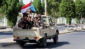 Southern Yemeni separatist fighters flash the V sign as they ride on the back of a truck in Aden yes