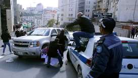 Palestinian activists throw tomatoes at a vehicle transporting members of an American economic deleg