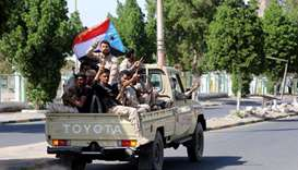 Southern Yemeni separatist fighters flash the V sign as they ride on the back of a truck in Aden.