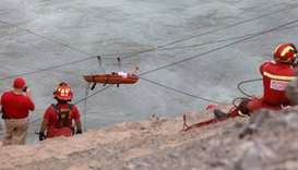 Rescue workers transport a victim after a bus crashed with a truck and careened off a cliff along a