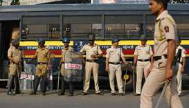 Policemen stand guard at a traffic junction in Mumbai