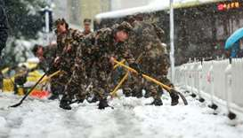 Chinese soldiers shovel snow to clear the road during a snowfall in Nanjing in China