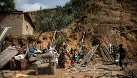 A child walks past (R) and a woman stands among the remains of a landslide in Ngaliema district on J