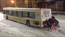 People push a bus on an icy road in Boston, Massachusetts