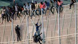 A member of the Spanish Civil Guard pulls a would-be immigrant off the border fence. File picture: