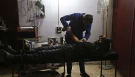 An injured Syrian man receives treatment at a makeshift hospital following reported air strikes in t