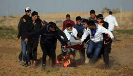 A wounded Palestinian demonstrator is evacuated during a protest at the Israel-Gaza border fence, in