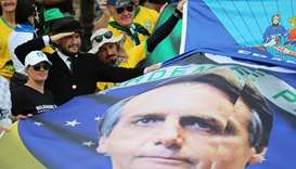 Supporters of Brazil's new President Jair Bolsonaro carry a banner with his portrait as they gather