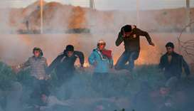 Palestinians run for cover from Israeli gunfire and tear gas during a protest at the Israel-Gaza bor