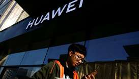 A man uses his phone as he walks past a Huawei shop in Beijing, China