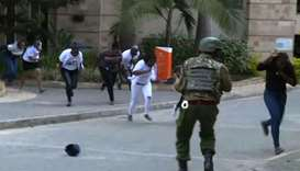 people running in a street as a gunfight was underway following a blast at a hotel and office comple