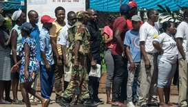 A Zimbabwean soldier watches a shopping queue, in Bulawayo