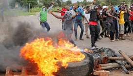 Protesters stand behind a burning barricade during protests on a road leading to Harare, Zimbabwe