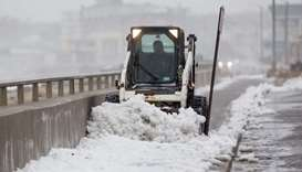 A worker uses a bobcat to clear snow from a sidewalk alongside Nantasket Beach