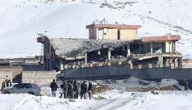Afghan men stand in front of a collapsed building of a military base after a car bomb attack in Maid