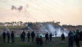 Tear gas canisters falling amidst Palestinian protesters during clashes with Israeli forces across t