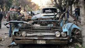 People gather at a site of a car bomb blast in Damascus, Syria