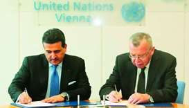 Al-Marri and Fedotov sign the agreement.