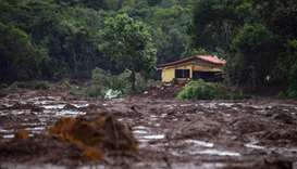 A damaged house is seen at the mud-covered area a day after the collapse of a dam at an iron-ore min