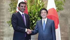 His Highness the Amir Sheikh Tamim bin Hamad Al-Thani shake hands with Shinzo Abe