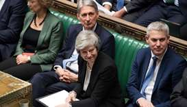 Theresa May (C) smiling in the House of Commons