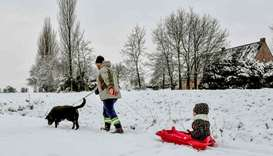 A person walks a dog and pull a kid on a luge on a snow covered road, Lille, France