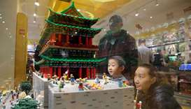 A boy and his mother look at the Zhengyang Gate Tower of Forbidden City made with Lego bricks at a L