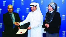 Dr Khalifa al-Khalifa (centre) receiving the accreditation certificates from Errol Persaud