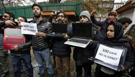 Kashmiri journalists display laptops and placards during a protest demanding restoration of internet