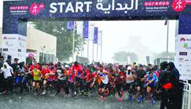 Runners of the Ooredoo Doha Marathon 2020 amid Friday's heavy downpour.