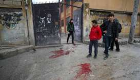 Syrians gather next to blood stains on the ground following a missile fired by Syrian regime forces