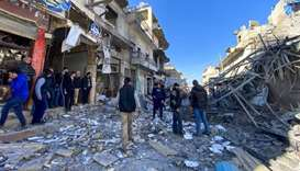 Syrians gather amidst the rubble following regime air strikes on a market in the town of Binnish in