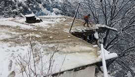 A boy clears a snow-covered roof of his family house after a heavy snowfall in Neelum Valley near li