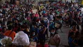 Evacuees from towns affected by the eruption of Taal volcano queue up at an evacuation center in Tan