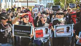 Activists hold up placards and shout slogans during a rally against Jakarta Governor Anies Baswedan