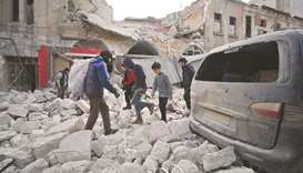 Syrians make their way through the rubble of a building following a regime air strike on Ariha town