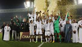 Al-Sadd's players celebrate on the podium with the Qatar Cup trophy after winning the final match ag