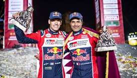 Qatar's Nasser Saleh al-Attiyah (right) and his French co-driver Mathieu Baumel pose with their runn