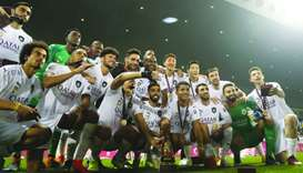 Al Sadd players pose with the Qatar Cup trophy after their 4-0 win over Al Duhail in the final