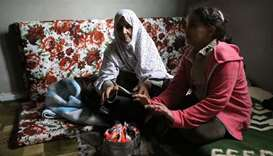 A displaced family warms up their hands at an unfinished apartment in Tripoli, Libya
