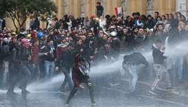 Demonstrators are hit by water canon during a protest against a ruling elite accused of steering Leb