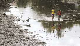 Two boys walk on a river filled with volcanic ash, following Taal volcano's eruption, in Lemery, Bat