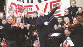 Conductor Michel Dietlin and members of the Paris Opera's orchestra play an improvised open-air conc