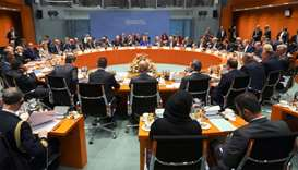 Overall view shows the participants sitting around a table with German Chancellor Angela Merkel (C,