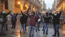 Lebanese anti-government protesters gather by a barricaded road leading to parliament in central Bei