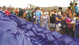 Residents, who refuse to evacuate, queue for relief goods following Taal volcano's eruption, in Tali